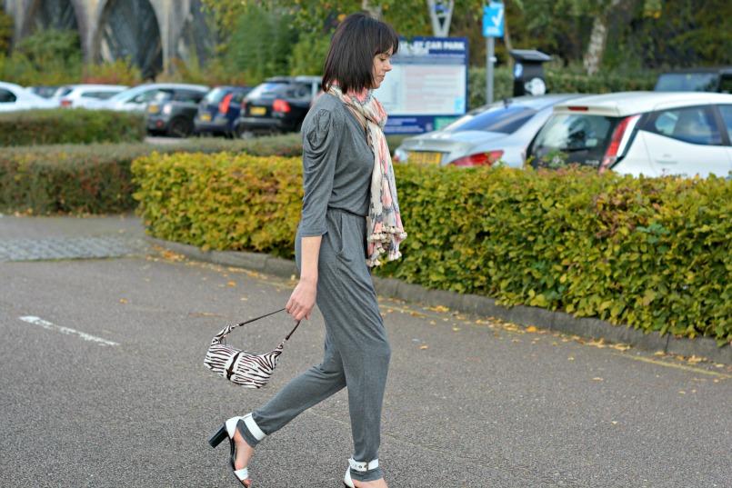 Sandro grey jumpsuit   Prada zebra pony hair bag   Whistles white two part sandal   All Saints Ikat pom pom scarf