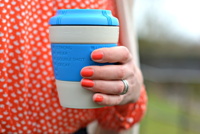 blue take away coffee cup and orange opi varnish