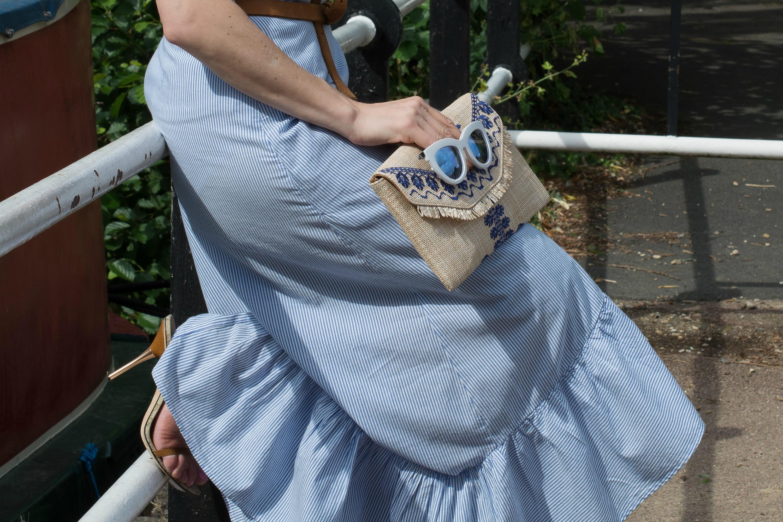 blue-pinstriped-cotton-skirt-raffia-clutch-bag